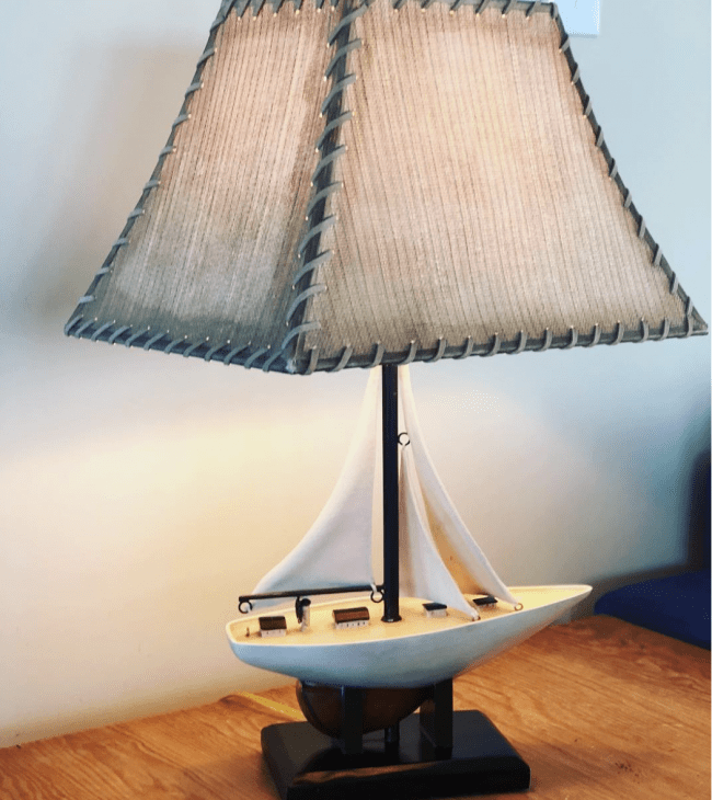 A sailboat themed lamp that is on top of a wooden table.