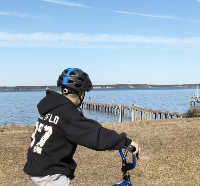 A boy sitting on his bike while looking  at a body of water.