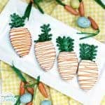 A white platter of carrot shaped decorated cookies.