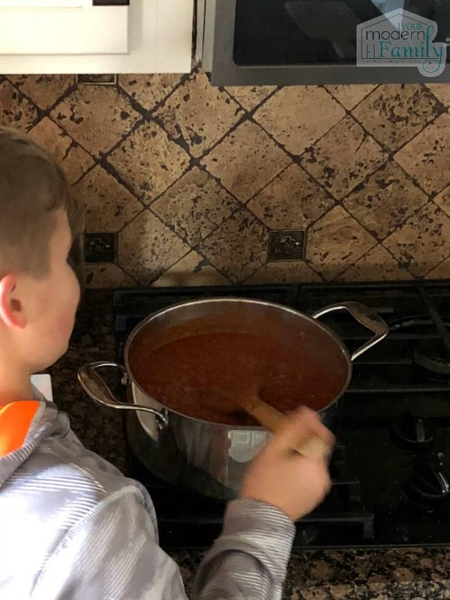 A little boy that is standing in front of a stove