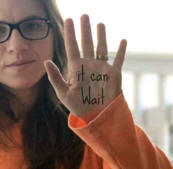 A woman holding up her hand that has words written on her palm.