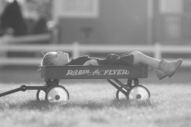 A boy laying in a wagon on top of a grass covered field.