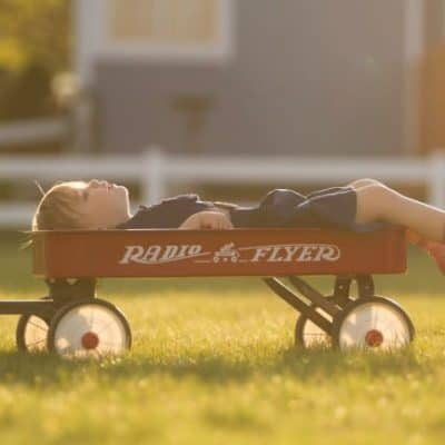 A young boy lying on a red wagon looking up to the sky.