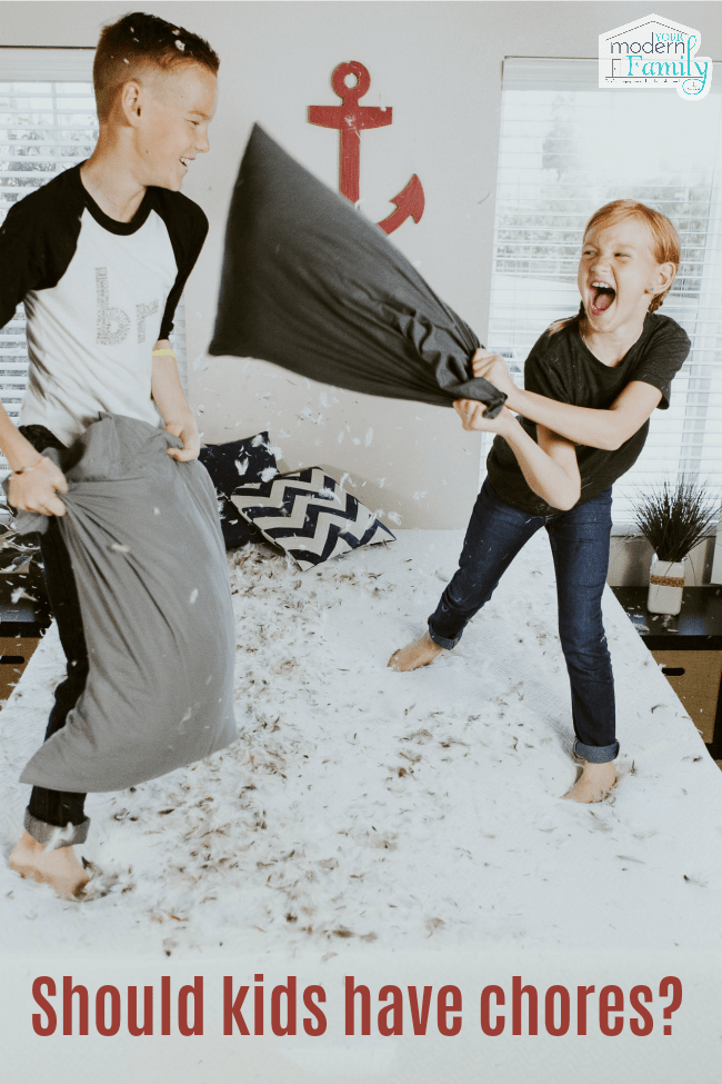 Two kids standing on a bed having a pillow fight.