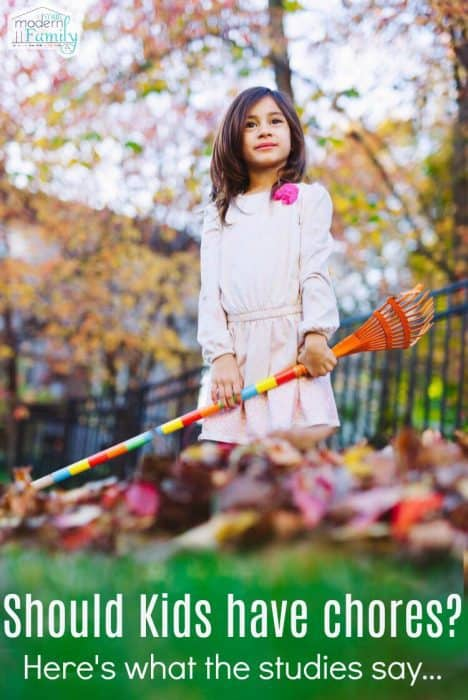 A girl holding a rake near a pile of leaves.