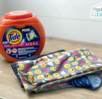 A container of Tide Pods detergent beside colorful children's clothes neatly folded.