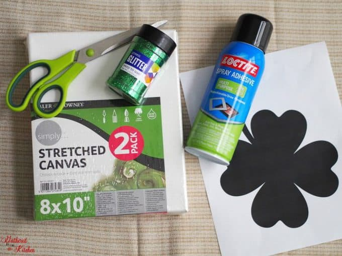 A variety of craft supplies including scissors, paper, glitter and a can of Loctite spray adhesive.