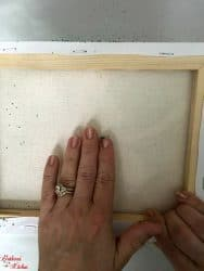 A close up of a persons hand placing a wooden frame on a white sheet of paper.