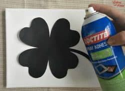 A close up of a black shamrock taped to a white piece of paper and a person spraying Loctite Adhesive on it.
