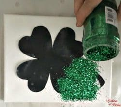 A person sprinkling green glitter on a black shamrock.