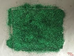 A picture of green glitter covering a whole sheet of white paper.