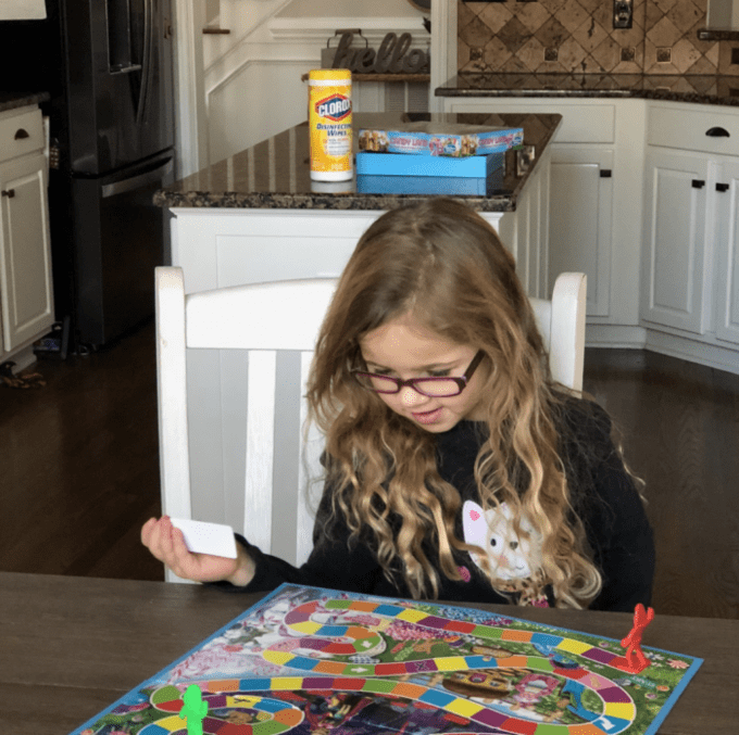 A little girl standing at the table playing a board game.
