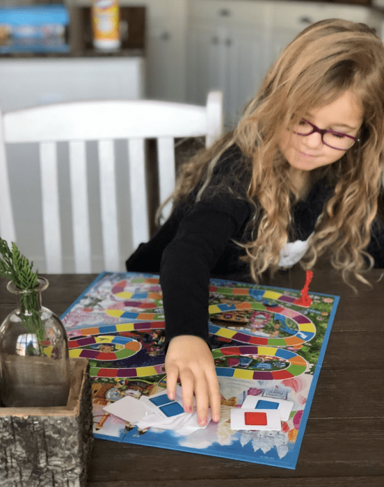 A little girl sitting at a table playing Candyland.