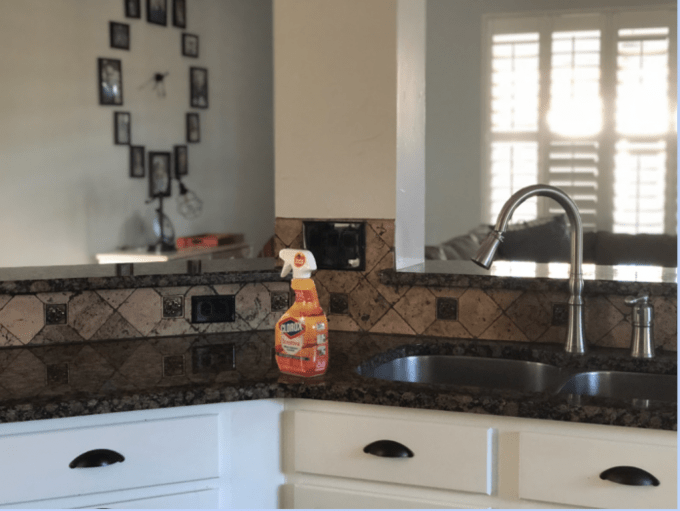 A kitchen counter with a spray  bottle of Clorox resting on it.