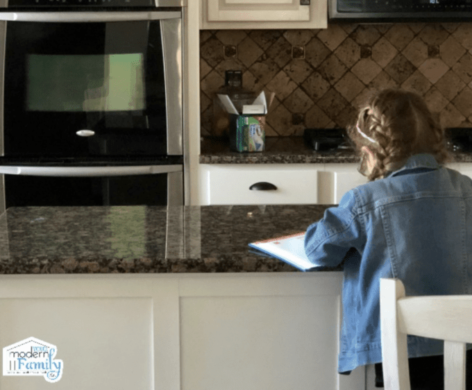 A little girl sitting at the kitchen counter doing paper work.