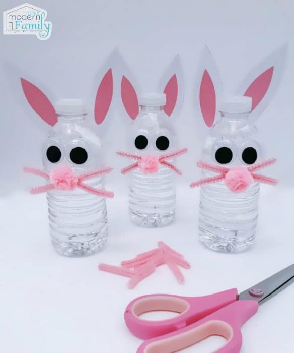 Three water bottles decorated as bunny rabbits with a pair of scissors lying in front of them.