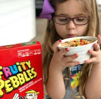A little girl holding a bowl of Fruity Pebbles microwave cake.