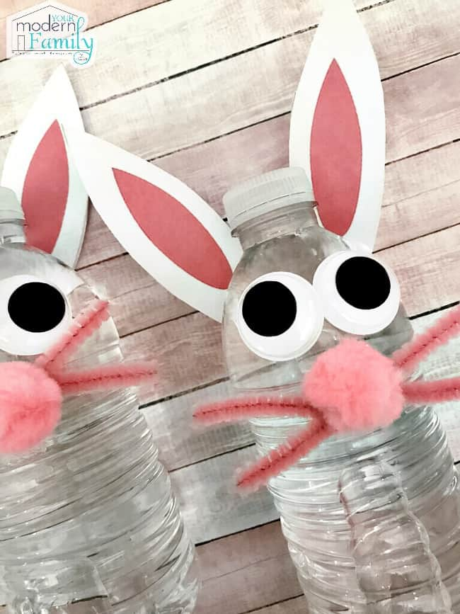 Two water bottles decorated to look like bunny rabbits lying on a table.