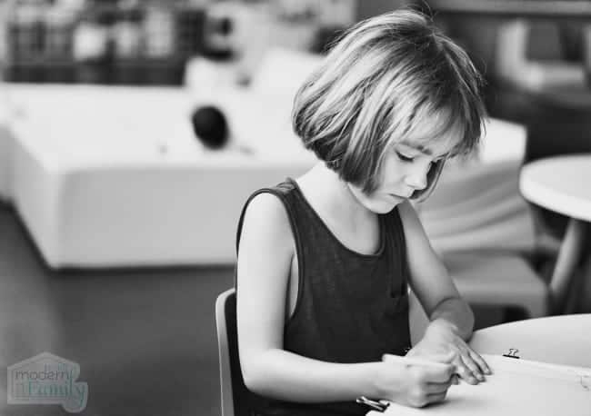 little girl writing Kindergarten Sight Words at a school table