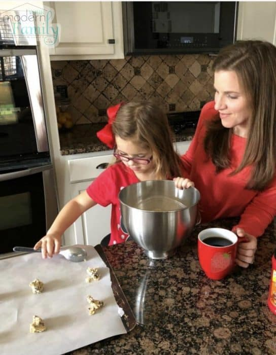 A women sitting at a table with a cup of coffee helping a little girl make cookies.