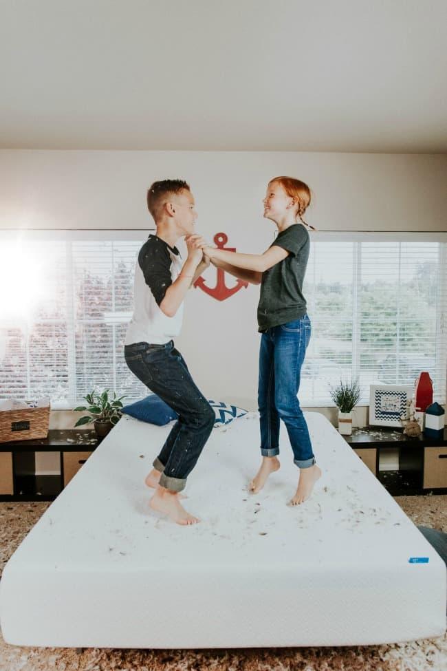 Two kids jumping on a mattress.