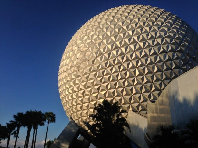 A picture of Epcot with palm trees around it.