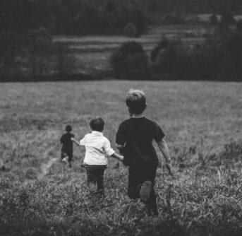 Little boys running down a hill of tall grass.