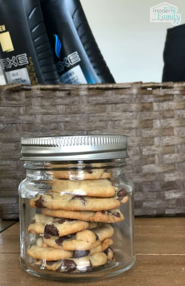 A clear glass jar with a metal lid and chocolate chip cookies in side of it.