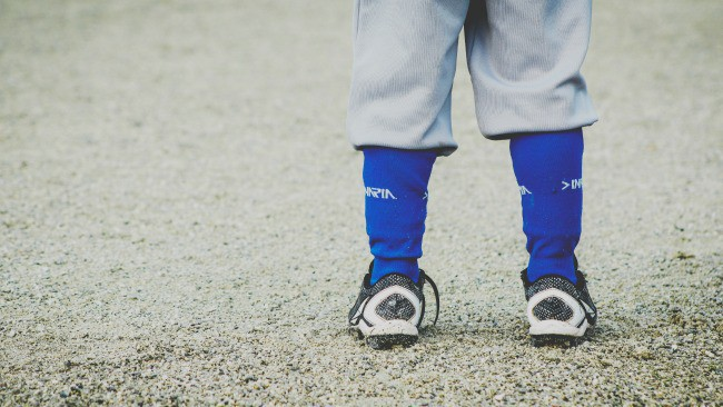 A little boy wearing baseball cleats and uniform.