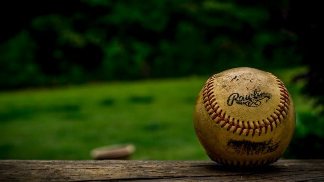 A close up of a baseball resting on a wooden fence.