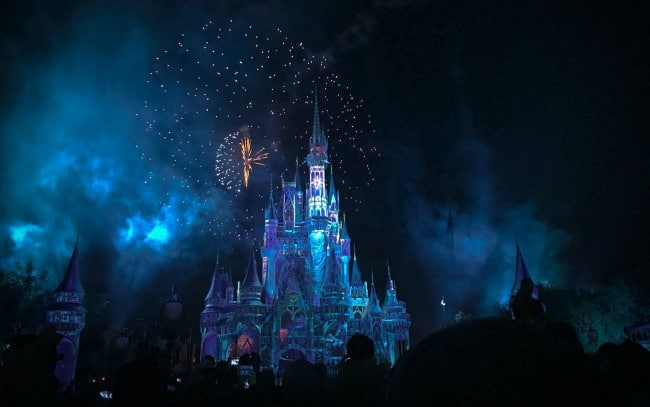 Cinderella\'s castle at night with fireworks in the background.
