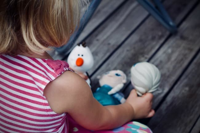 A little girl playing with Frozen character toys.