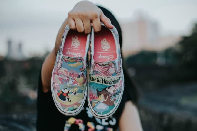 A girl holding a pair of tennis shoes decorated with Disney characters.