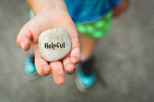 """A child with a flat rock in their open hand with \""""Helpful\"""" written on it."""