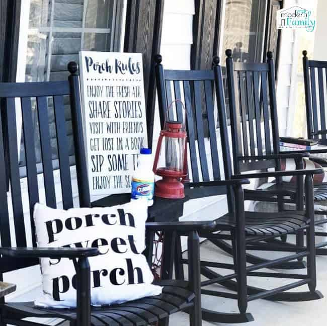 Numerous black wooden rocking chairs on a porch.
