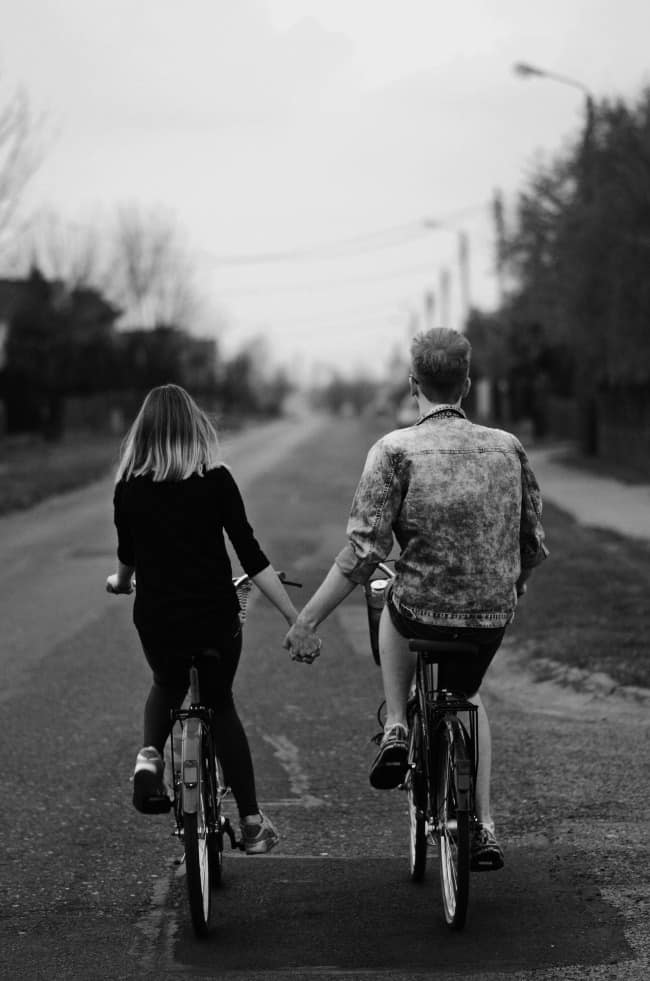A young woman and a young man holding hands while riding bicycles down the street.