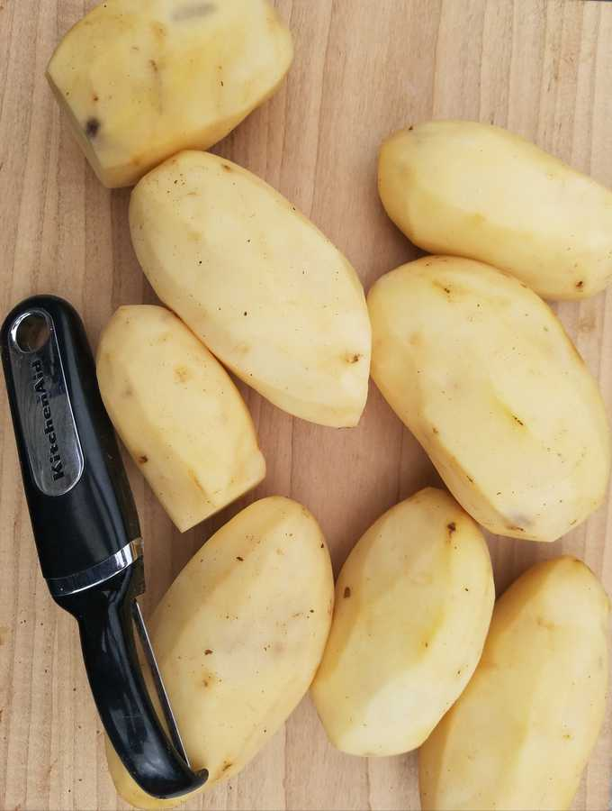 Numerous  peeled potatoes and a black peeler sitting on a table.