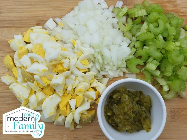 A variety of chopped vegetables and a cup sitting on a table.