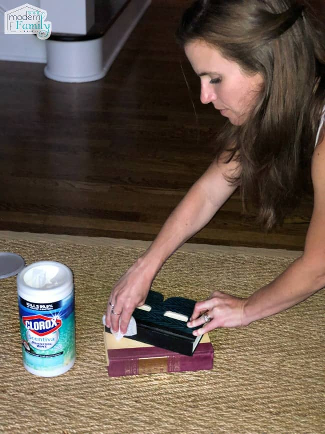 A woman wiping clean book covers with Clorox wipes.