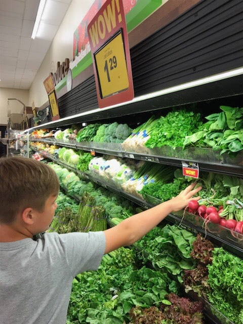 A young boy reaching for produce in a grocery store.