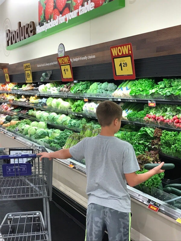 A boy standing in front of a produce stand.