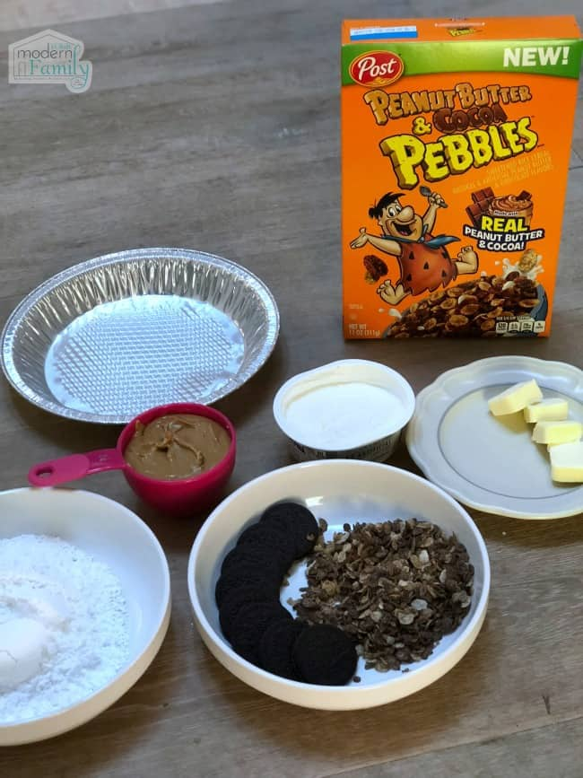 A variety of ingredients in bowls and measuring cups with a box of cereal behind them.