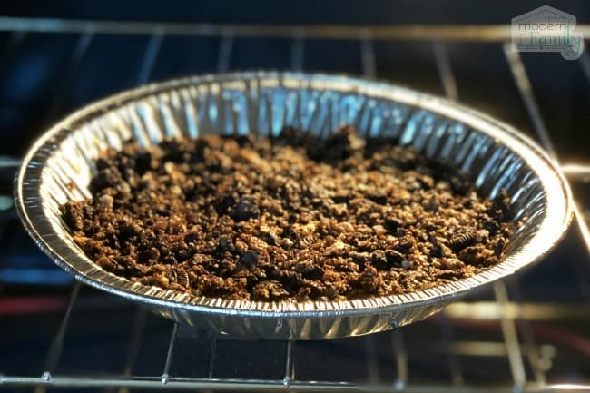 A close up of a metal pan in the oven with crushed cereal in it.