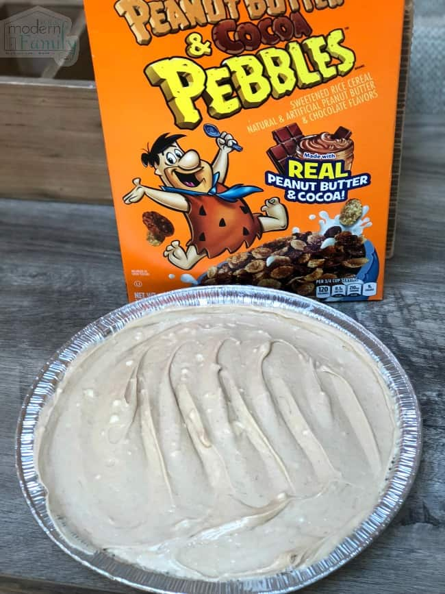 A finished Peanut Butter and Cocoa Pie sitting in front of a box of cereal.