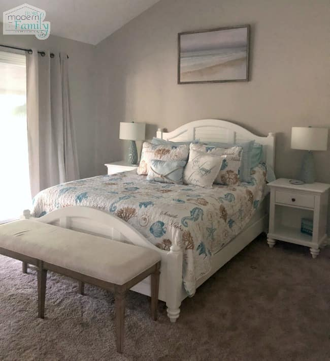A bedroom with a bed and desk decorated with a coastal theme.