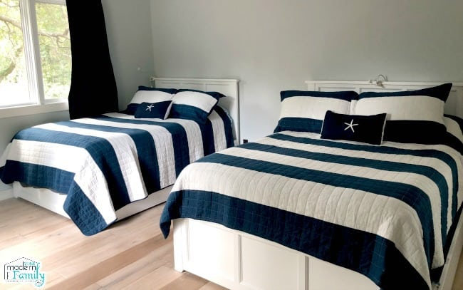 Two beds with blue and white striped comforters with sand dollar accent pillows.