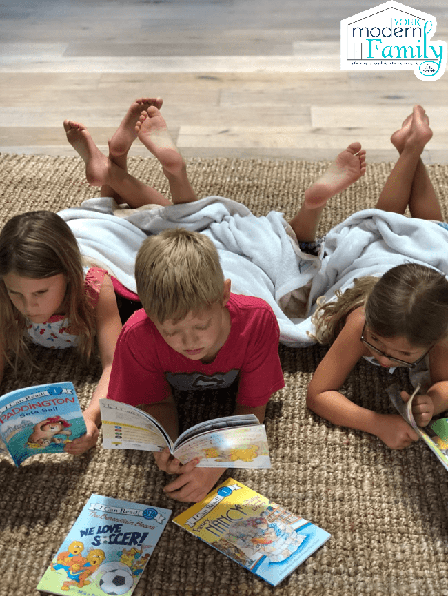 three kids reading books on the floor