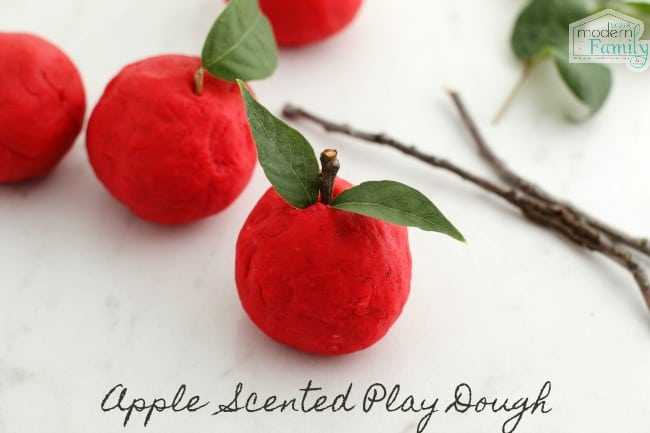 Balls a red play dough decorated to look like apples.