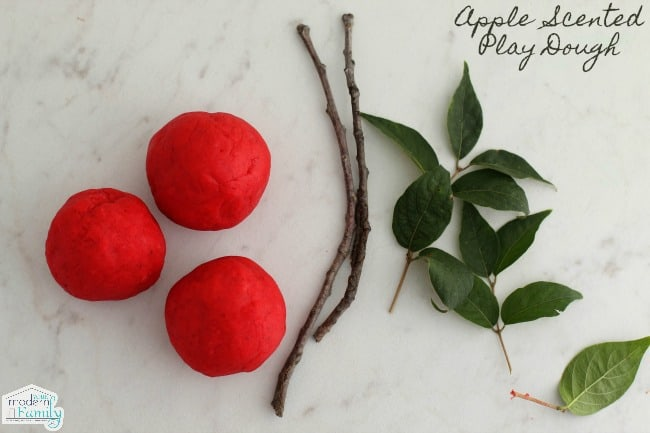 A close up of red play dough balls, twigs and leaves to make play dough apples.