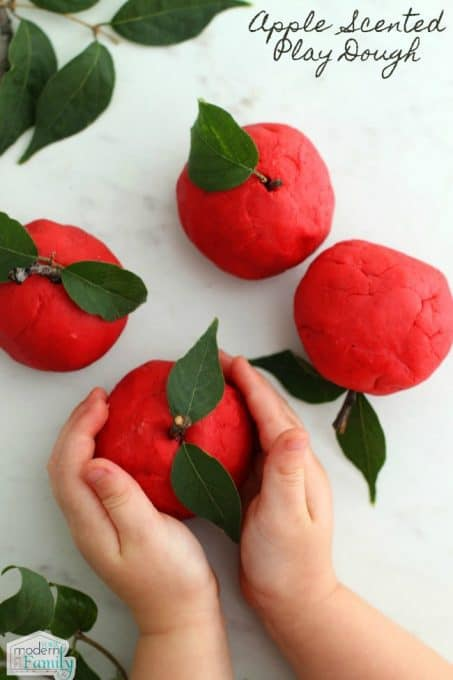 A close up of a hands holding red play dough apple craft.